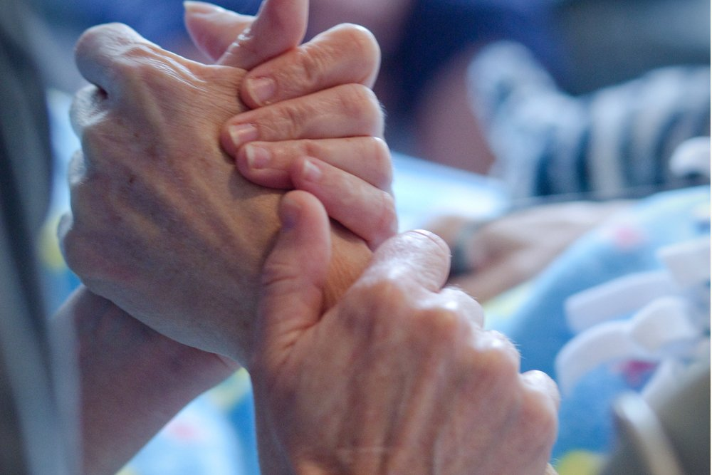 hands clasped at a hospital bedside, representing difficult emotions