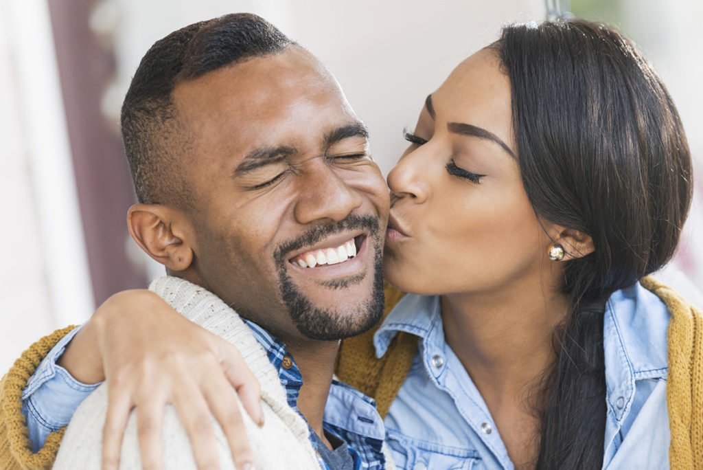 Young couple, woman kissing her boyfriend on cheek