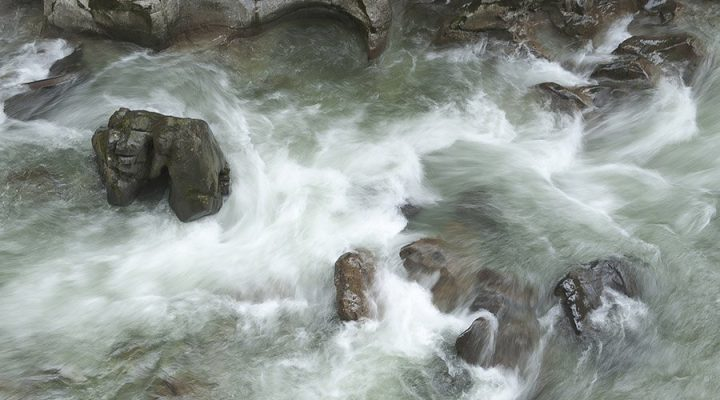 rocks in torrential river water, as metaphor for negative emotions